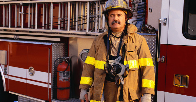 Firefighter Standing Next to Fire Engine