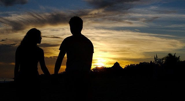 Silhouette Of Young Couple Holding Hands
